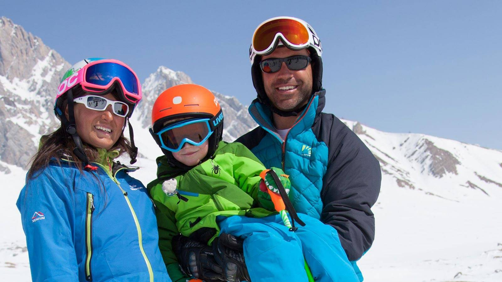 A child has fun on the snow with his parents