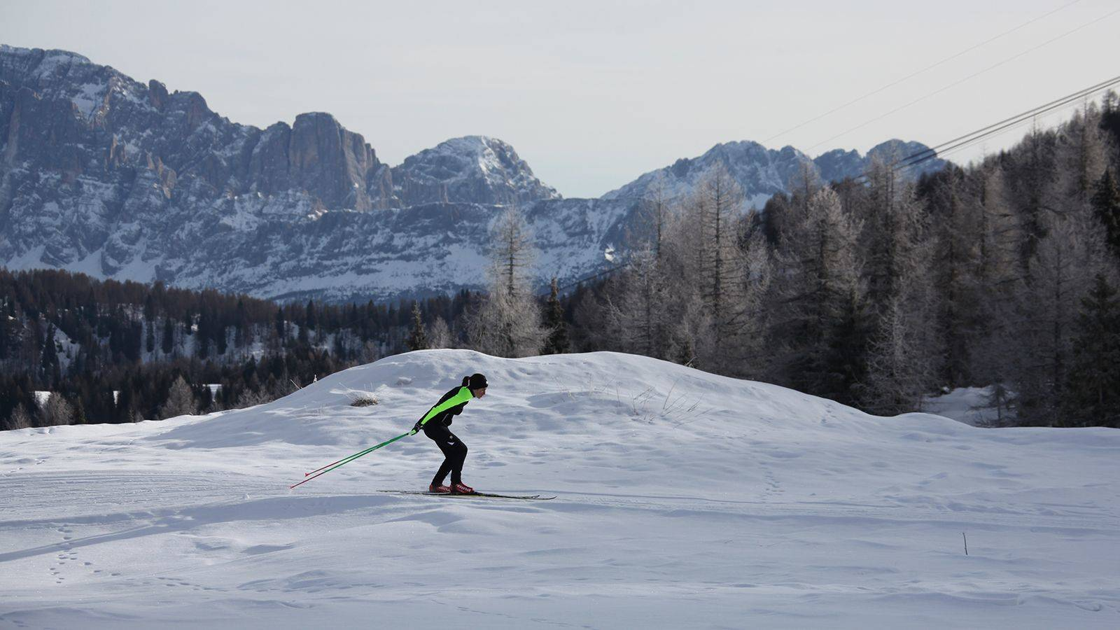 A girl practicing Nordic skiing at the snowy slopes of Passo San Pellegrino