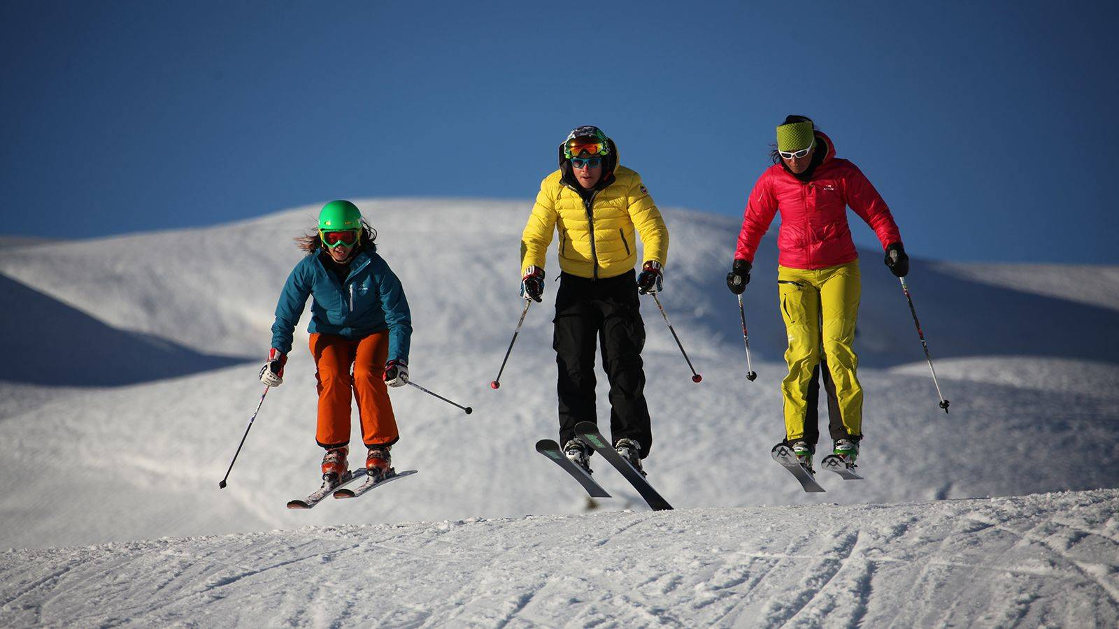 A family during a ski jump on the slopes of Passo San Pellegrino