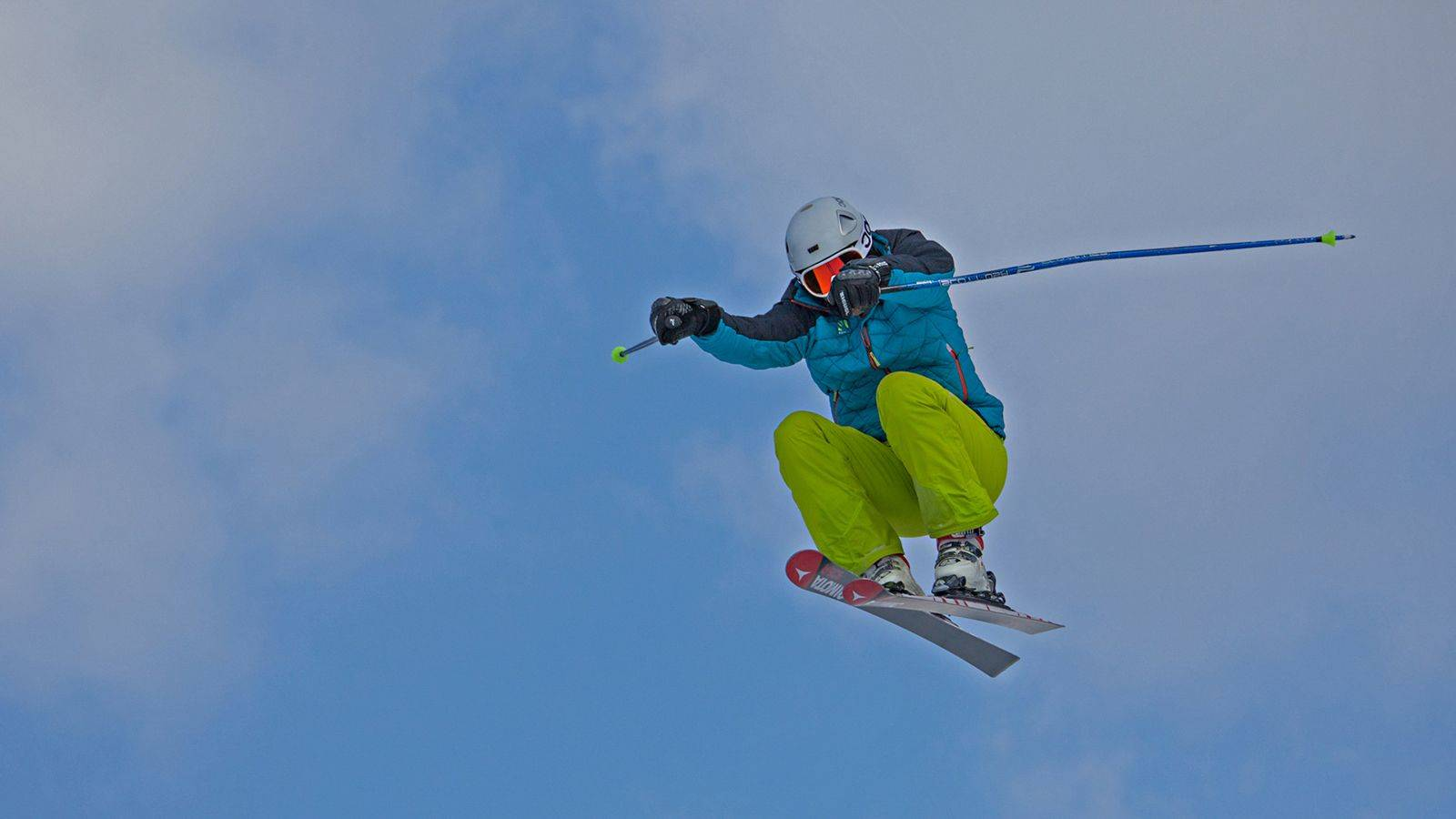 A skier does a stunt on the ski slopes of Passo San Pellegrino