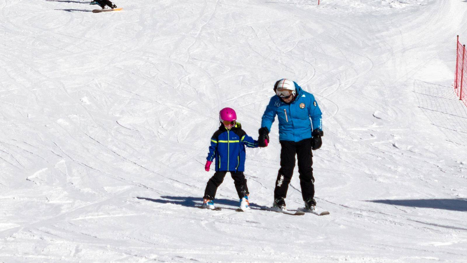 A teacher takes a child by the hand and teaches him how to ski