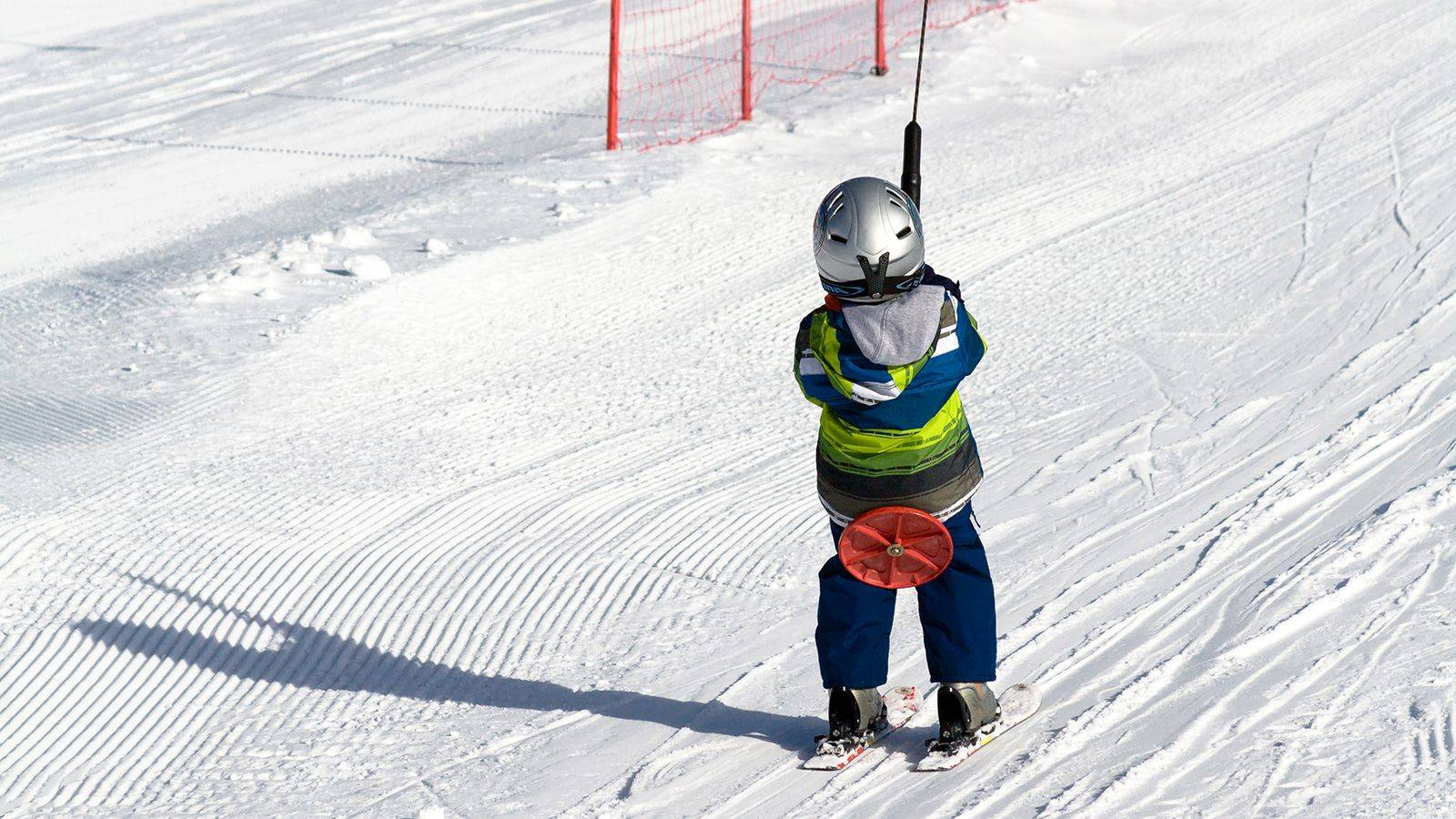 A child learns to go on the ski lift at Passo San Pellegrino